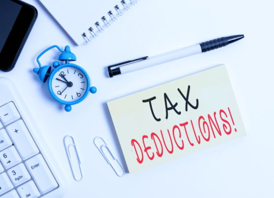Text sign showing Tax Deductions. Business photo text reduction income that is able to be taxed of expenses Flat lay above computer mobile phone clock pencil and copy space note paper